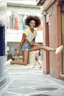 Happy woman with afro hairstyle jumping in a lane - JSMF00009