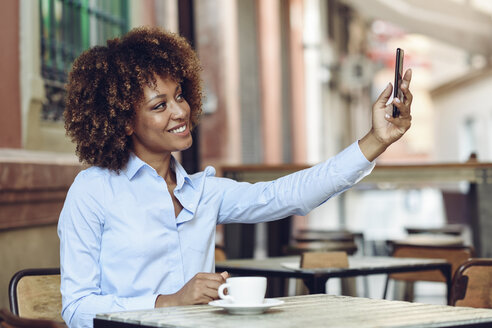 Smiling woman with afro hairstyle sitting in outdoor cafe taking a selfie - JSMF00015