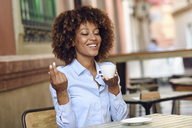 Smiling woman with afro hairstyle sitting in outdoor cafe drinking coffee - JSMF00018