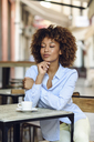 Relaxed woman with afro hairstyle sitting in outdoor cafe - JSMF00024