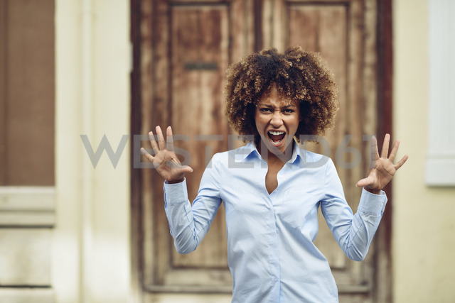 Portrait of woman with afro hairstyle screaming outdoors - JSMF00033