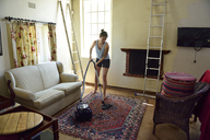 Young woman renovating her home hoovering - ECPF00184