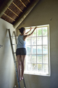 Young woman renovating her home working at window frame - ECPF00187