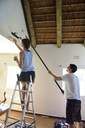 Young couple renovating their home painting the wall together - ECPF00196