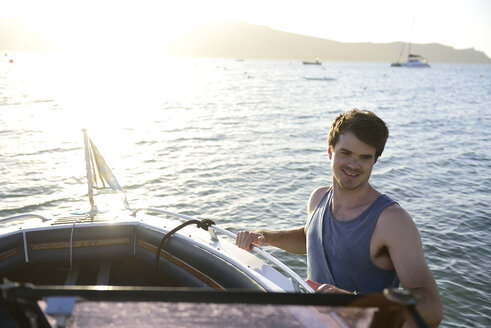 Smiling young man on a boat in the sea - ECPF00202