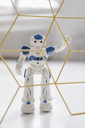 Miniature robot figurine standing behind structure - FLAF00147
