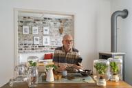 Senior man making glass biotopes at home - LAF01971