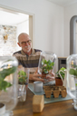 Senior man making glass biotopes at home - LAF01977