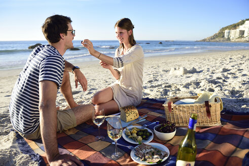 Happy couple having a picnic on the beach - ECPF00208