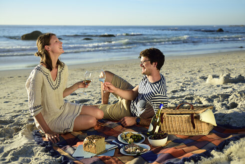 Happy couple having a picnic on the beach - ECPF00211