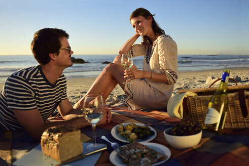 Happy couple having a picnic on the beach - ECPF00214