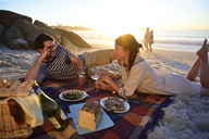 Happy couple having a picnic on the beach at sunset - ECPF00217