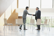 Chairs surrounding businessmen shaking hands - CAIF01243
