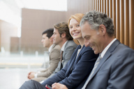 Portrait of smiling businesswoman sitting with businessmen - CAIF01252