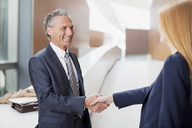 Smiling businessman shaking hands with businesswoman - CAIF01258