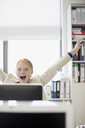 Exuberant businesswoman at computer in office - CAIF01279