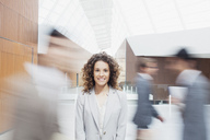 Portrait of smiling woman with co-workers rushing by in lobby - CAIF01282