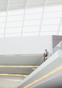 Businessman standing at glass balcony railing in modern building - CAIF01297