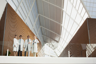 Portrait of smiling doctors at glass railing of balcony in modern building - CAIF01303
