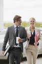 Smiling businessman and businesswoman walking with coffee cups - CAIF01306