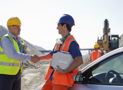 Worker and businessman shaking hands in quarry - CAIF01354