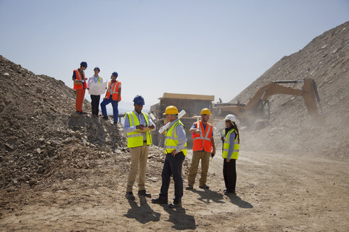 Business people and workers talking in quarry - CAIF01357