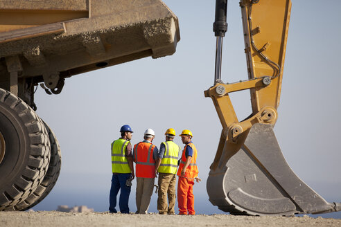 Workers talking by machinery in quarry - CAIF01399