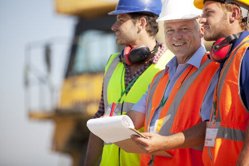 Businessman and workers talking on site - CAIF01402