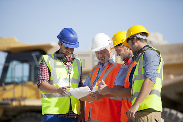 Workers and businessman talking in quarry - CAIF01414
