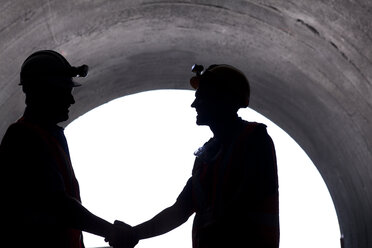 Silhouette of workers shaking hands in tunnel - CAIF01435