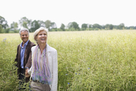 Couple walking in field of tall grass - CAIF01438