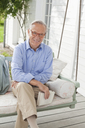 Smiling man sitting on porch swing - CAIF01441