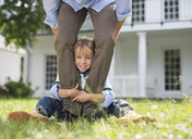 Boy peeking out from between father's legs - CAIF01444