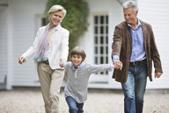 Couple walking with grandson outdoors - CAIF01459