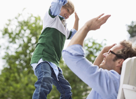 Father and son high fiving outdoors - CAIF01462