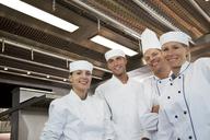 Chefs smiling in restaurant kitchen - CAIF01510