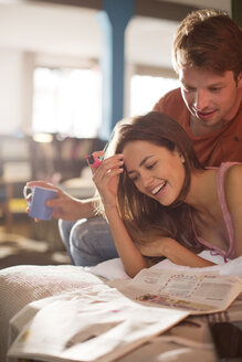 Couple reading newspaper together - CAIF01516