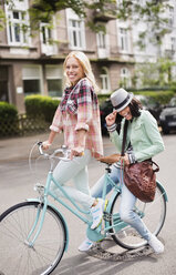 Women riding bicycle together on city street - CAIF01519