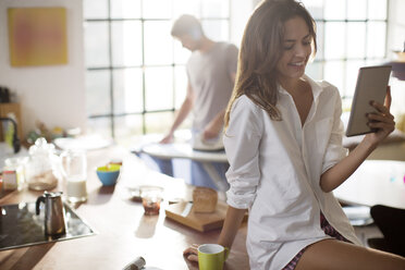 Woman using digital tablet in kitchen - CAIF01525