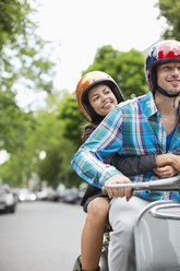 Couple riding scooter together - CAIF01528