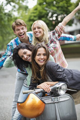 Friends smiling on scooter outdoors - CAIF01546