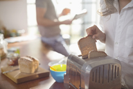 Woman putting bread in toaster - CAIF01549