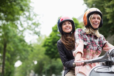 Women riding on scooter together outdoors - CAIF01552