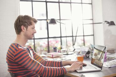 Man using laptop at desk - CAIF01564