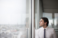 Businessman looking out office window - CAIF01579