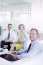 Business people talking in office lobby area - CAIF01591