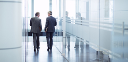 Businessmen talking in office hallway - CAIF01603