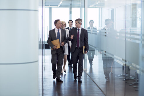 Businesspeople walking in hallway - CAIF01627