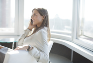 Businesswoman talking on phone in office - CAIF01630