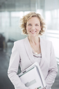 Businesswoman smiling in office hallway - CAIF01645